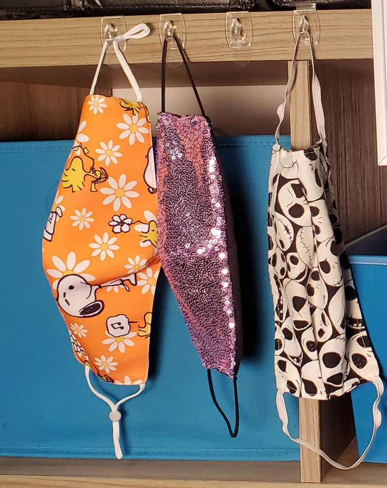 assorted face masks hanging on organizer